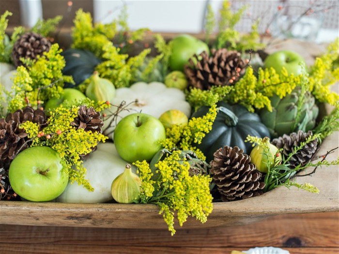 pine cones and green apples, very pale and dark green pumpkins, and tiny yellow flowers, in an oval wooden dish, thanksgiving wishes