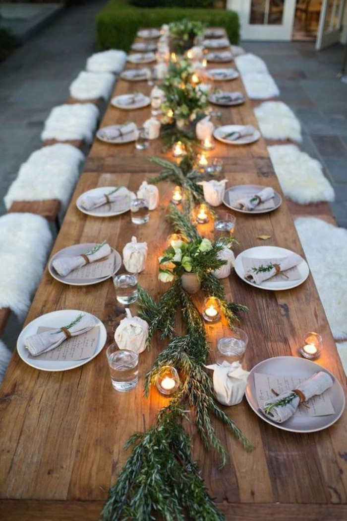eighteen plates with napkins, placed on a long, rustic wooden table, decorated with green branches, and tea lights
