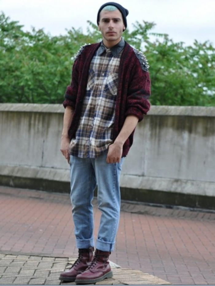 punk and grunge outfit, inspired by 90s bands, featuring light blue ankle jeans, burgundy combat boots, a plaid shirt, and a dark purple cardigan with leather shoulder details, decorated with spikes, on a young man, with light blue hair, and a black beanie hat