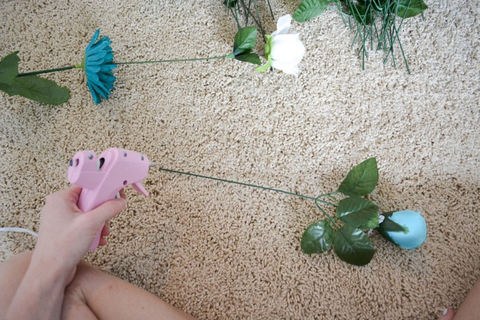 glue gun in pink, held by a pale hand, near a faux blue rose, with green plastic leaves, and a long stalk, diys for your room, more fake flowers nearby