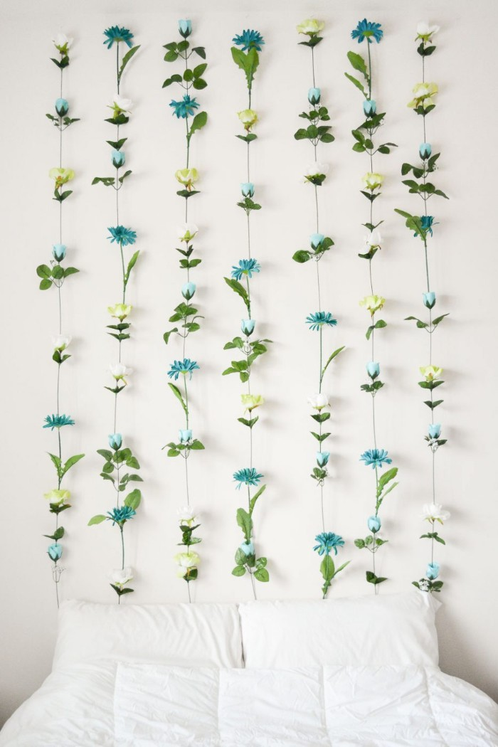 blue and light yellow, and white faux flowers, with green leaves, and long plastic stems, glued together in seven columns, and attached to a white wall, near a bed