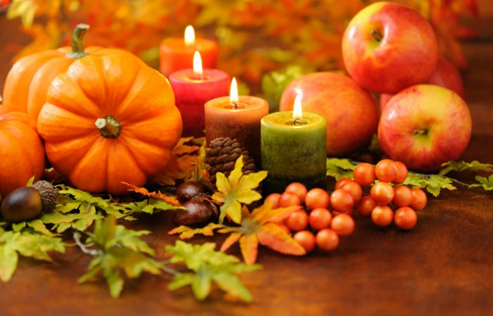 apples and four lit candles, faux pumpkins and fall leaves, conkers and pine cones, thanksgiving messages for friends, red faux berries