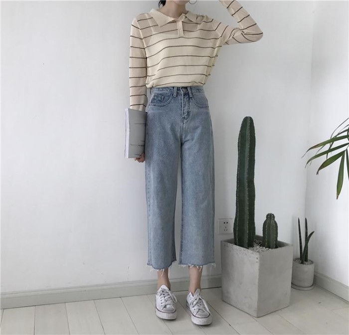 cutoff ankle jeans, in pale blue acid wash denim, worn with a white tank top, under a sheer, striped vintage-style shirt, grunge definition, on a slim woman, with well-worn white converse trainers