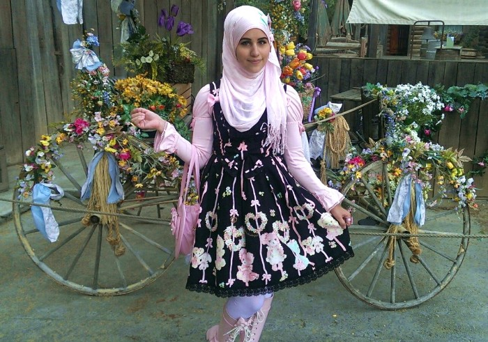 muslim sweet lolita, in a pale pink hijab, wearing a black dress, with a cutesy pattern in pastel colors