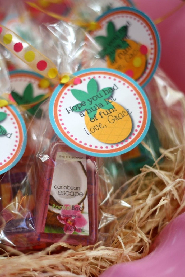 party favor idea, small bottles of coconut body lotion, wrapped in clear plastic, and decorated with a round label, featuring a pineapple, and the words hope you had a hula lot of fun, 50th birthday themes, hawaiian luau party