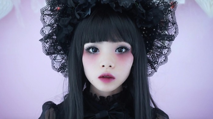 very pale japanese lolita, with pink eyeshadow and lipstick, seen in close up, wearing a semi sheer, frilly blouse and a black lace bonnet