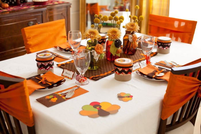 children's thanksgiving table, white tablecloth and orange napkins, brown plates with white pollka dots, three vases in different colors, containing yellow flowers, cheap centerpiece ideas, multicolored turkey shaped paper cutouts