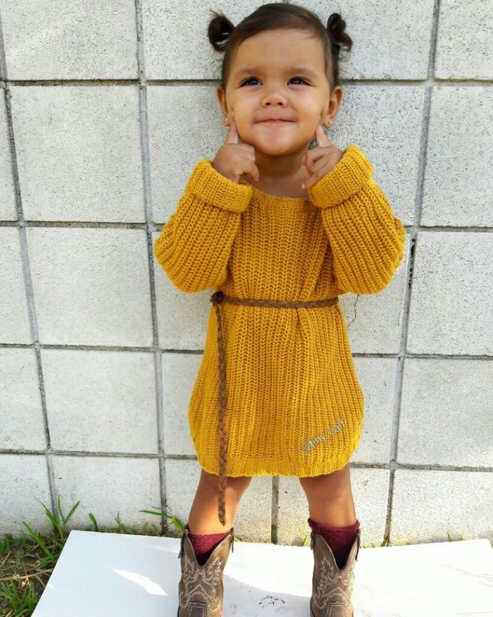 yellow knitted jumper dress, worn with a woven, thin brown leather belt, and cowboy boots, by a small child, girls thanksgiving outfit, simple and cute
