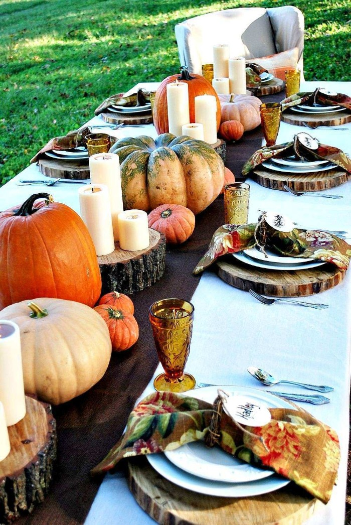 grassy lawn near a thanksgiving table, with round natural wood place mats, candles and assorted pumpkins