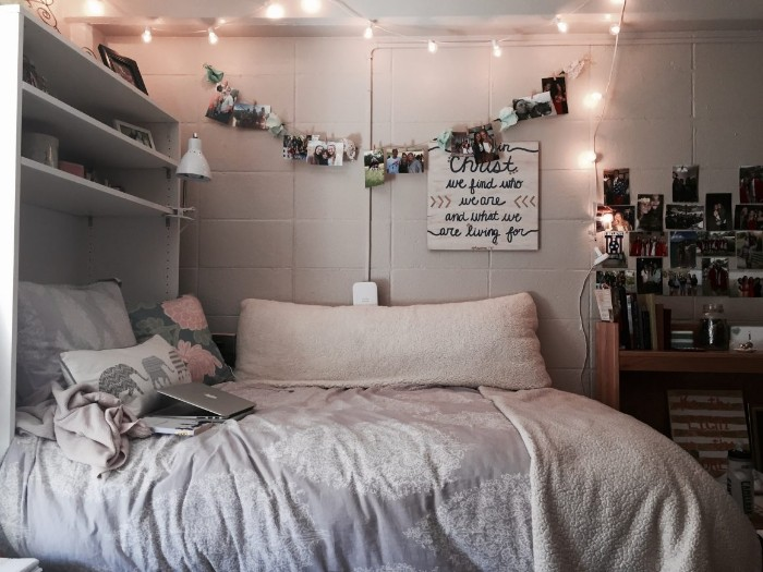lit string lights, hanging over a bed, with light cream, and pale grey, covers and pillows, in a dim room, with shelves and wall decorations