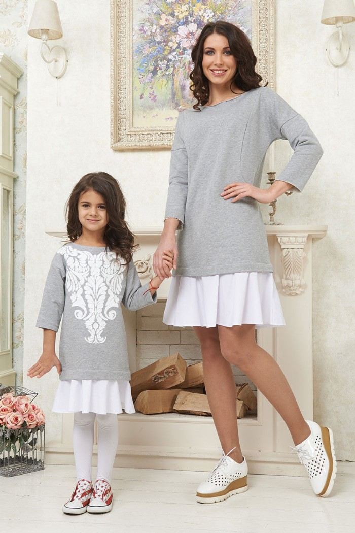 daughter and mother holding hands, dressed in almost identical, cute thanksgiving outfits, long pale grey jumpers, with quarter sleeves, over white mini skirts