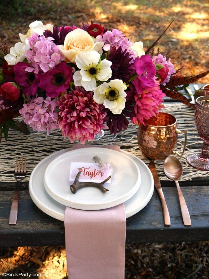 copper mug and two stacked white plates, topped with a small dark brown antler, and a name card, pale pink napkin, and some cutlery, on a table, decorated with a large bouquet