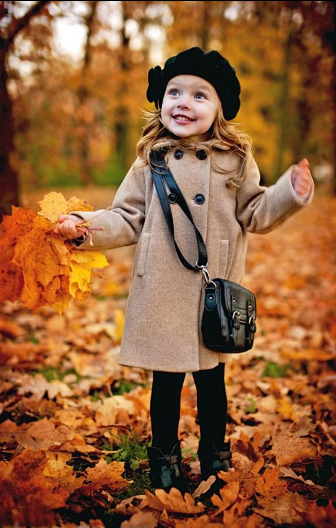 girls thanksgiving outfit, smiling female toddler, wearing a beige winter coat, black leggings and a black hat, with a black cross body bag