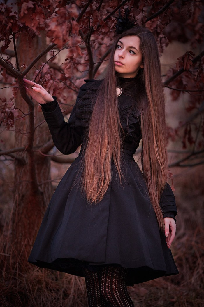 slim young woman, with long brunette hair, wearing a frilly, black gothic lolita dress, with a cameo brooch