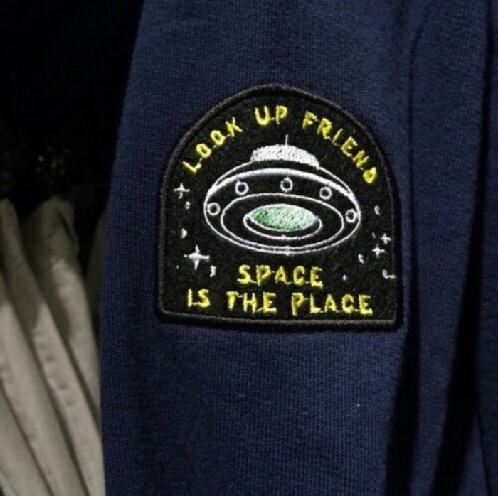 patch in black, featuring a flying saucer, and the words look up friend, space is the place, embroidered in white, yellow and pale green, 90s grunge accessories, sewn on a dark blue fabric