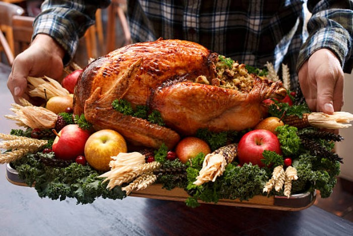 trey containing a large roasted turkey, on a bed of green vegetables, decorated with apples and corncobs, berries and dried wheat stalks, thanksgiving text messages, held by a man, dressed in a plaid shirt