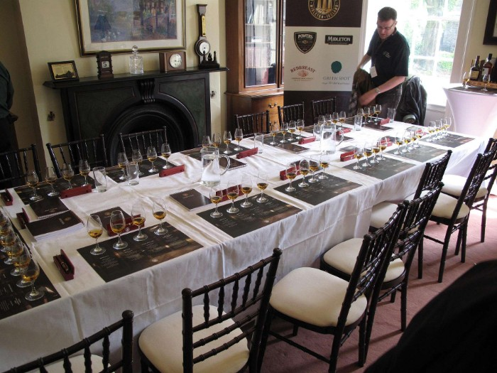 long rectangular table, with several place mats, each containing four glasses, containing some whiskey, 50th birthday celebration ideas for husband, whiskey tasting event