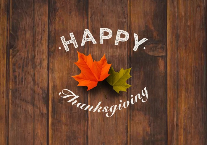 small green leaf, and a larger orange leaf, on a wooden surface, with the words happy thanksgiving, superimposed in white