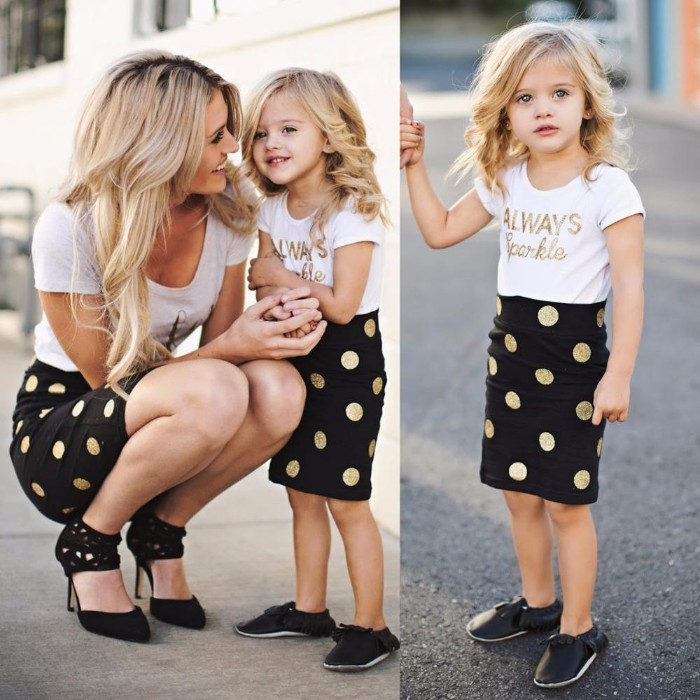 gold polka dots, on identical black skirts, worn by a mother and her small daughter, toddler thanksgiving outfit, similar white t-shirts, and different black shoes