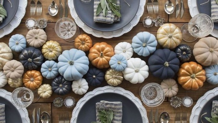 many faux pumpkins, in pale blue and dark navy, white and beige, orange and gold, decorating a wooden table, with large dark blue plates, cheap centerpiece ideas, seen from above