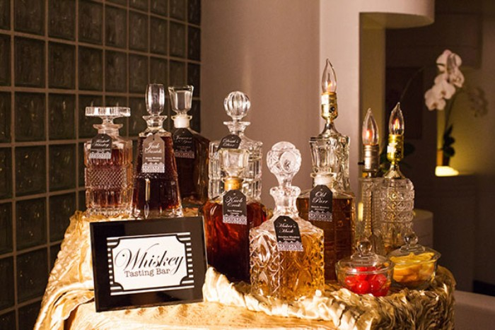 50th birthday celebration ideas for husband, a selection of whiskeys, in different ornamental glass bottles, on a small round table, with a shiny gold tablecloth