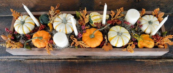 six white candles, in different shapes, placed in a narrow wooden crate, containing white and orange pumpkins, gourds and fall leaves, thanksgiving centerpiece, on a dark brown wooden table