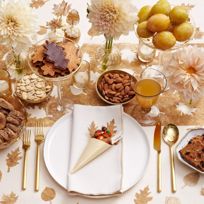 bisquits and fruit, nuts and seeds, in various dishes, placed on a white tablecloth, decorated with pale beige leaves, thanksgiving table setting, white plate and napkin, gold cutlery and a glass with juice