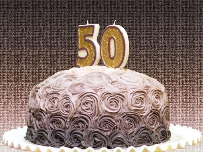 birthday cake in three shades of grey, with frosting shaped like multiple roses, and two candles covered in gold glitter, and shaped like the numbers 5 and 0