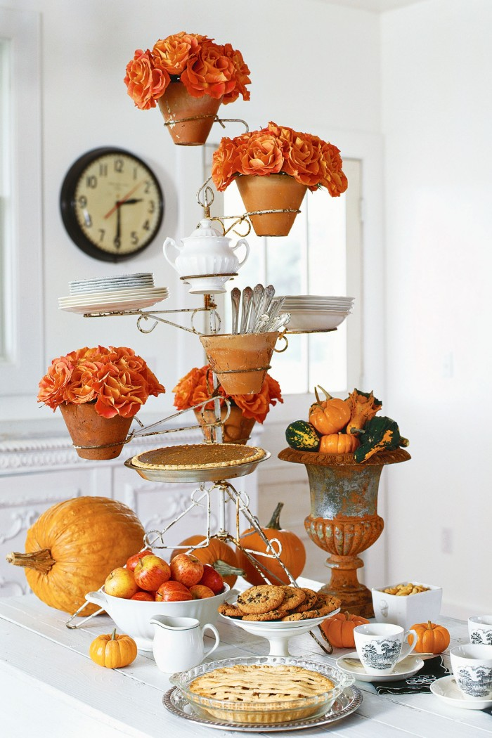 ceramic pots filled with orange flowers, placed on a metal stand, with a pie, some cutlery and plaates, and a white pot, thanksgiving table decorations