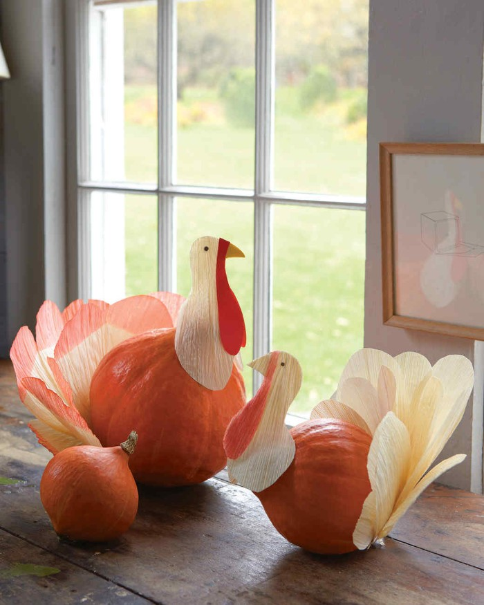 turkey decorations, made from two orange pumpkins, and paper cutouts, placed on a dark brown wooden surface