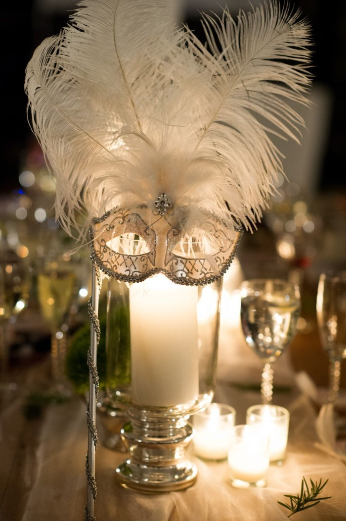 venetian-style mask in white, decorated with silver glitter, and large white ostrich feathers, placed on a glass container, with a large lit candle, 50th birthday ideas, fancy masked ball
