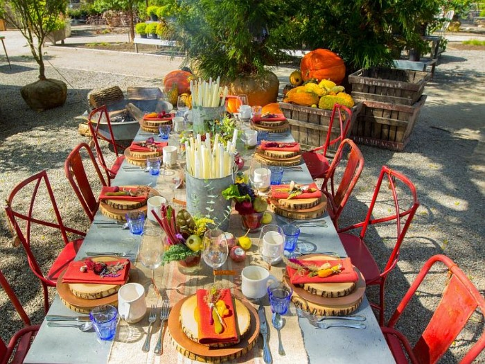 red chairs near a pale blue, rectangular dinner table, set for eight people, and placed outdoors, decorated with two buckets, filled with candles, and bowls of fall vegetables
