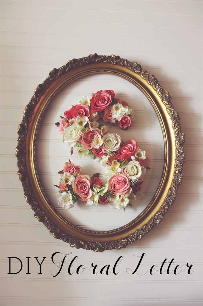 ornamental frame with an oval shape, painted in gold, containing the letter s, teenage girl room ideas, decorated with cream, and pink faux flowers