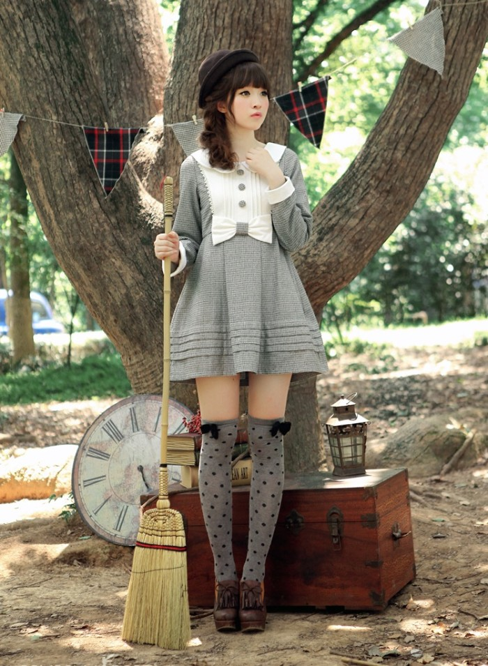 japanese lolita, in a light grey mini dress, featuring a white bib detail, a peter pan collar, and a bow on the waist line, grey over-the-knee socks, with black polka dots and bows