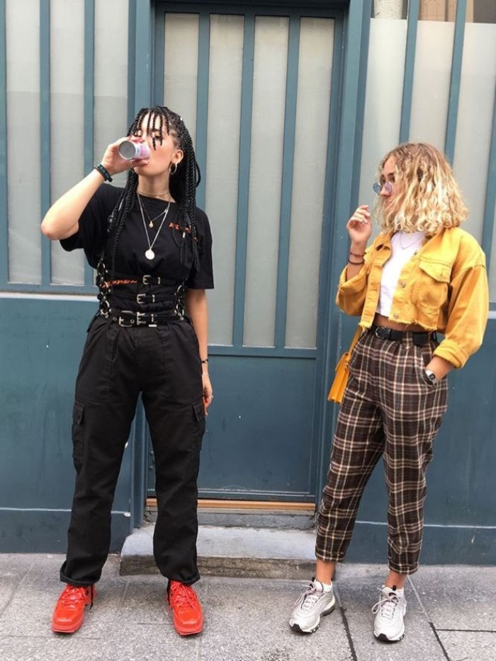 two young women, dressed in 90s grunge fashion, one wearing a black outfit, with multiple belts and red sneakers, the other in checkered ankle trousers, white cropped top, and a cropped yellow jacket