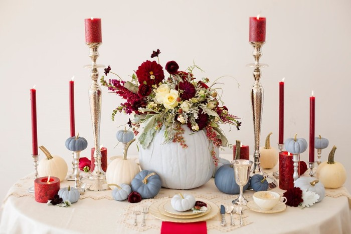 burgundy red candles in different sizes, and small blue faux pumpkins, on a round table, with plates and cups, cheap centerpiece ideas, large light blue hollow pumpkin, filled with burgundy red and cream flowers