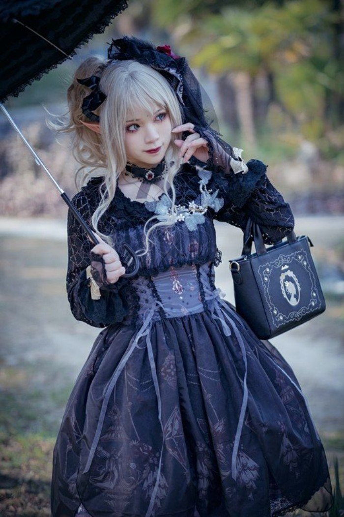 gothic lolita dress in black, worn by a pale girl, with faux elf ears, and a platinum blonde wig