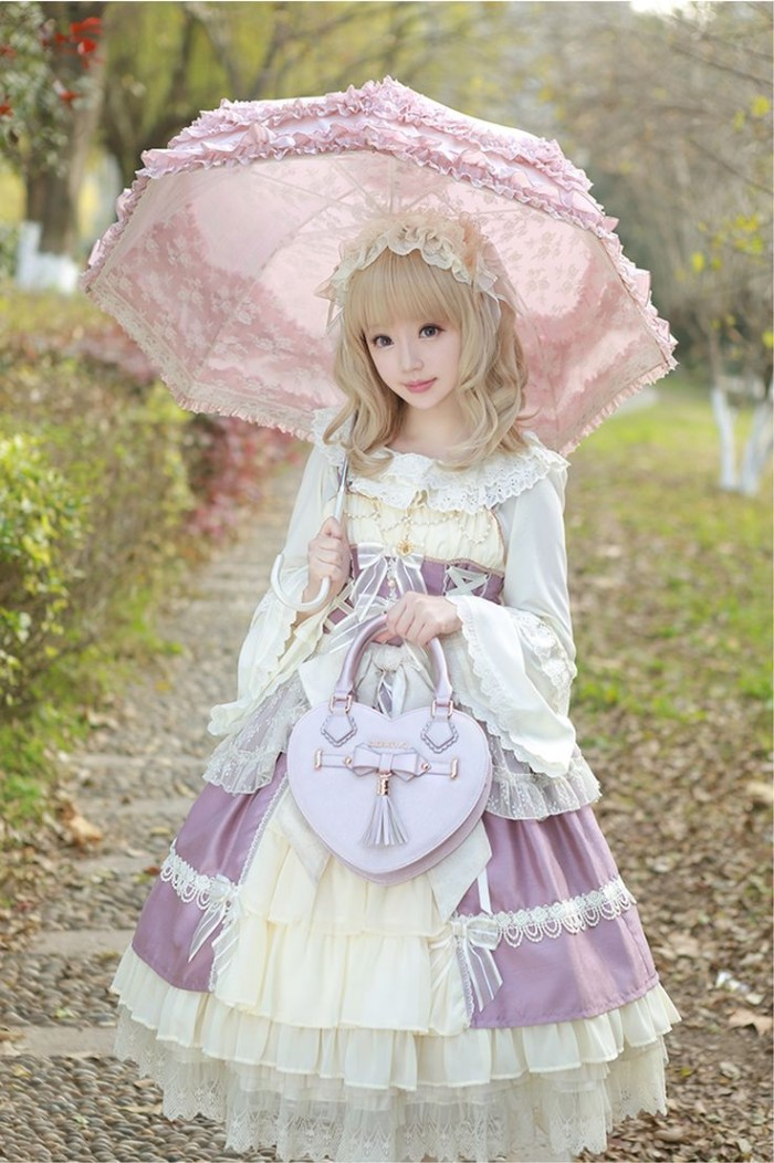 sweet lolita dress, in pale purple, off white and cream, worn by a girl, in a straw blonde wig, holding a pink frilly parasol