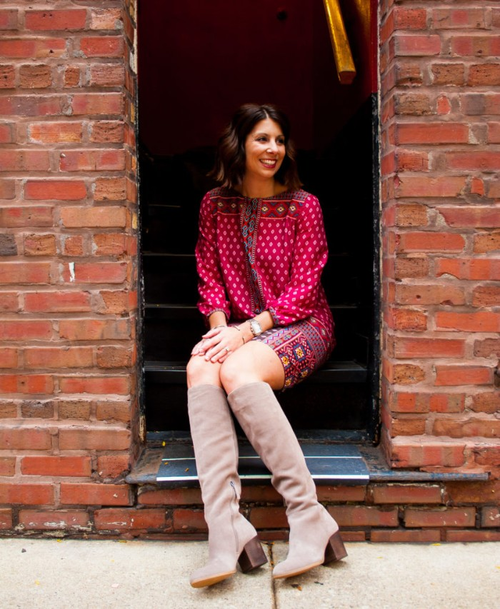 creamy grey tall suede boots, on a smiling brunette woman, with short wavy hair, dressed in a red patterned mini dress, comfy outfits for the holidays