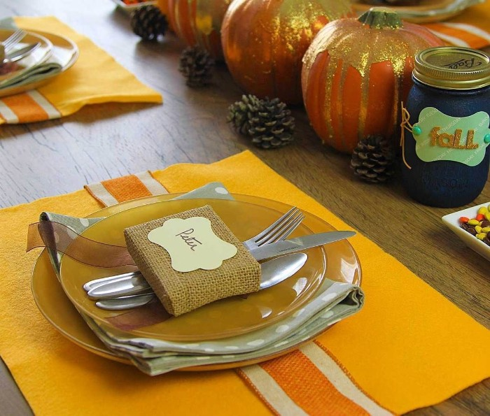 close up of two stacked, dark yellow plates, with a pale grey napkin between them, cutlery and a small square object, wrapped in brulap and decorated with a name tag, placed on top, thanksgiving tablescape