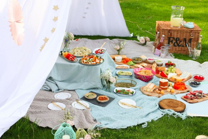 50th birthday ideas, green lawn with several blankets, covered in various dishes, large white fabric tent-like structure, picnic basket and decorations