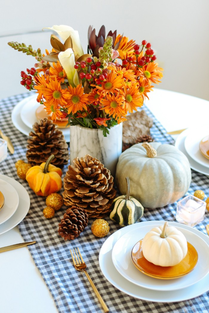 bouquet with orange, white and red flowers, in a marble vase, surrounded by pumpkins in different sizes, pinecones and yellow baubles, thanksgiving table decorations, plates and cutlery