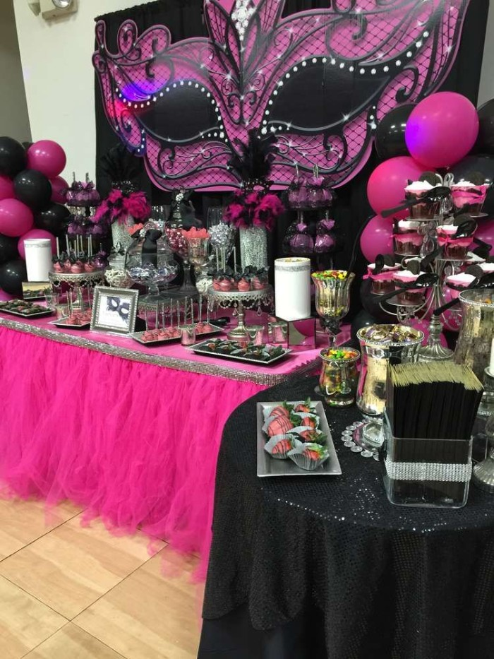 hot pink and black tables and decorations, for a masked ball-themed party, 50th birthday colors, pink balloons and a large, mask-shaped wall decoration, in black and pink