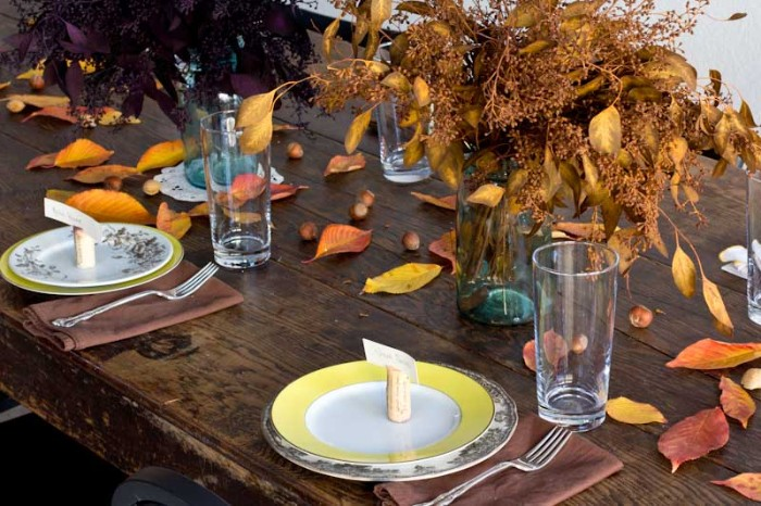 vintage dark brown wooden table, with yellow and white plates, each containing a small name card, propped up on a cork bottle stopper, bouquets of dried plants, yellow and orange, red and brown leaves strewn about the table