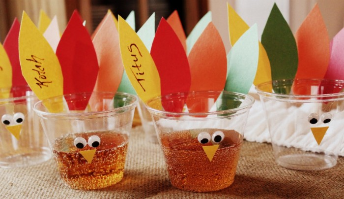 cups made out of clear plastic, decorated with eye stickers, and pieces of paper, in yellow and red, orange and green, turkey decorations for your party