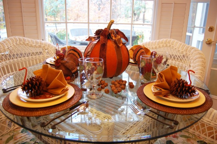 dishes decorated with turkey ornaments, made from pinecones, orange pipe cleaners, and yellow napkins, folded like fans, on a round glass table, near a large pumpkin, and a turkey figurine
