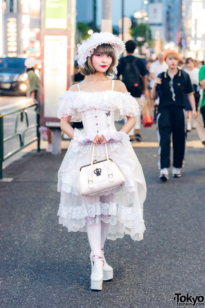 bonnet in white, with lacy frills, worn by a japanese lolita, in a tiered, off-the-shoulder white lace dress