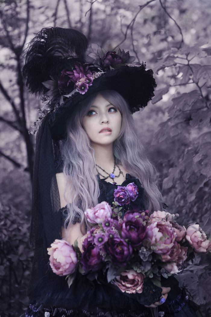 wavy platinum blonde hair, on a pale woman, wearing an extravagant black hat, with large feathers and faux flowers, black gothic dress, large bouquet of pale pink, and purple flowers