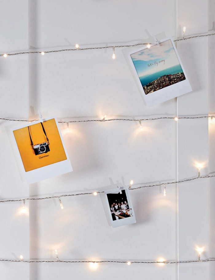 three colorful polaroid photos, attached to lit string lights, with smal clothes pegs, cheap ways to decorate a teenage girl's bedroom
