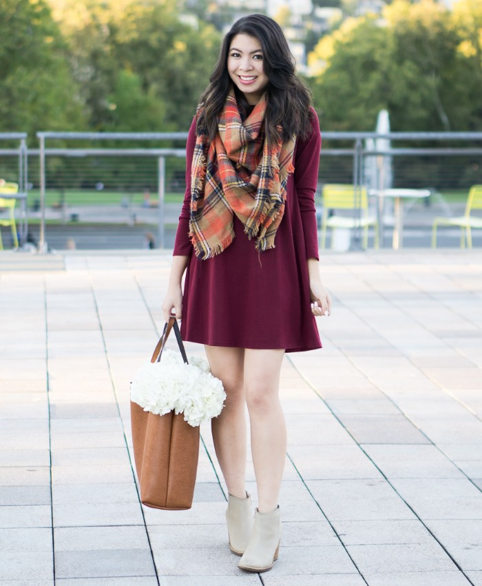 thanksgiving outfits, plaid blanket scarf, in beige and red, black and white, worn over a burgundy mini dress, with pale grey ankle boots
